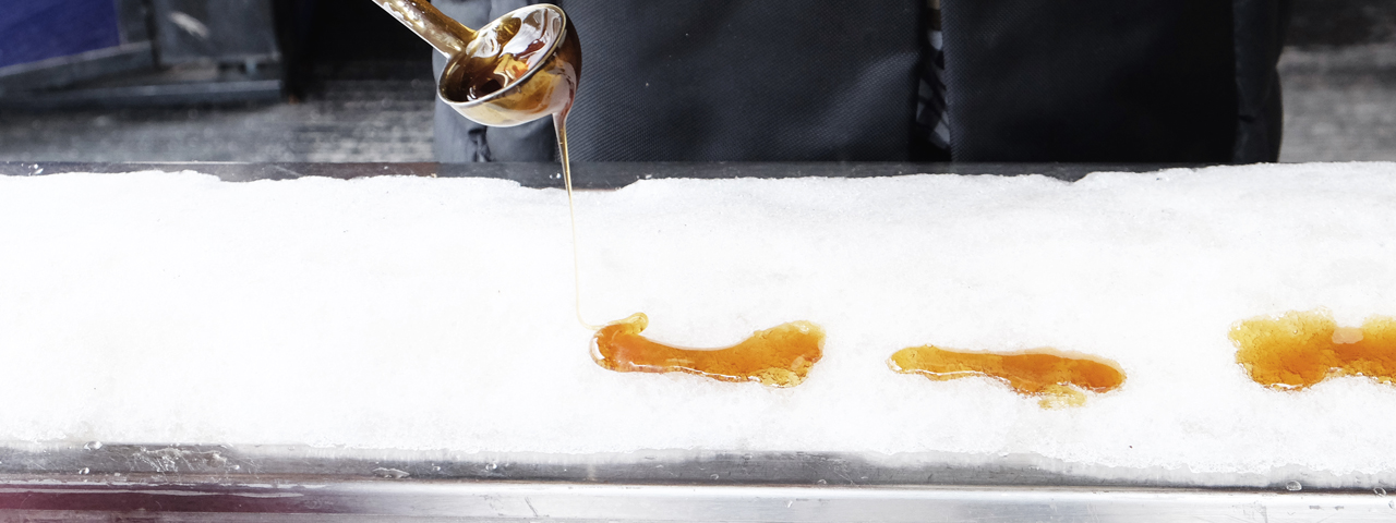 Pooring hot syrup from a spoon on ice to cool it down. Sugars and syrups are part of our Food Solutions Ingredients we offer in Confectionary.