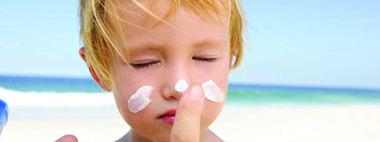 Child being rubbed with sunprortection that contains all sorts in skin care ingredients provided by Caldic